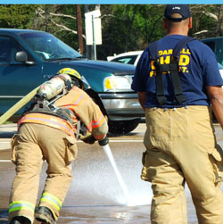 Fire fighter putting all his weight into carrying the charged hose forward.
